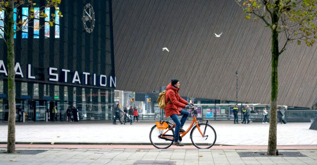 Fietser-voor-Rotterdam-Centraal-Station-op-oranje-fiets-van-Donkey-Republic