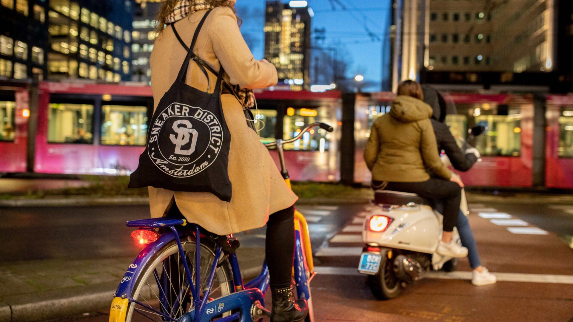 Vrouw op fiets met daarachter een scooter en tram